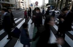 "Pedestrians walk past a ""no U-turn"" traffic sign as they cross a street at a business district in Tokyo, Japan, February 19, 2016. REUTERS/Yuya Shino"