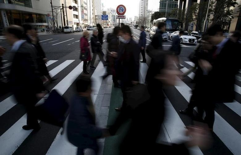 Pedestrians walk past a ''no U-turn'' traffic sign as they cross a street at a business district in Tokyo, Japan, February 19, 2016. REUTERS/Yuya Shino