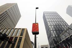 """Una bandera china cuelga de un poste entre dos edificios en un centro financiero de Tianjin. Imagen de archivo. 22 de febrero de 2016. Moody's Investors Service bajó el miércoles la perspectiva de la calificación de China a """"negativa"""" desde """"estable"""", citando la incertidumbre sobre la capacidad de las autoridades para implementar reformas, una creciente deuda del Gobierno y  menores reservas. REUTERS/Jason Lee"""