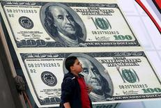 A boy walks past an exchange bureau advertisement showing images of the U.S dollar in Cairo, Egypt, Feburary 21, 2016. REUTERS/Mohamed Abd El Ghany