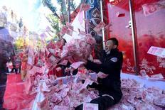 Мужчина пытается поймать деньги в стеклянной клетке во время празднеств по случаю наступающего Праздника весны в парке развлечений в Ханчжоу. 26 января 2016 года. Китайские инвесторы вложили $1,03 триллиона в зарубежную собственность, акции и облигации за десятилетие, завершившееся в середине 2015 года, сообщила в среду британская компания по управлению имуществом Knight Frank в своем ежегодном докладе. REUTERS/Stringer