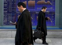 Hombres caminan junto a un tablero electrónico que muestra los índices de mercado de varios países, afuera de una correduría en Tokio, Japón,  2 de marzo de 2016. Las bolsas de Asia subían el miércoles a máximos en dos meses luego de que unas ganancias en los precios del petróleo en la sesión anterior y una serie de datos económicos positivos desde Australia a Estados Unidos redujeron el temor a una desaceleración económica mundial. REUTERS/Thomas Peter