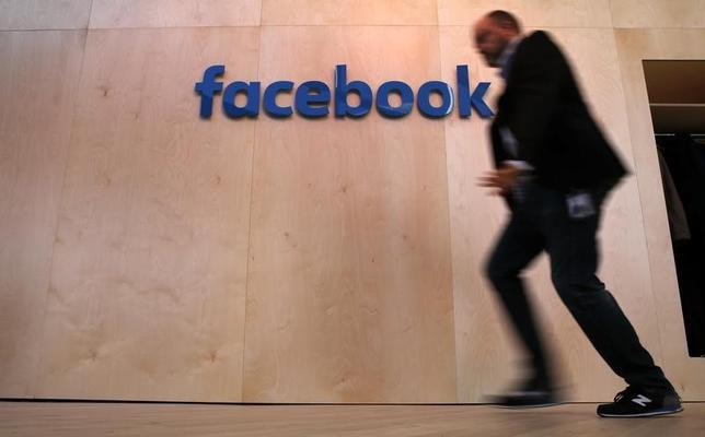 A man walks in front of the Facebook logo at the new Facebook Innovation Hub during a preview media tour in Berlin, Germany, February 24, 2016.      REUTERS/Fabrizio Bensch