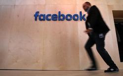 Un hombre camina frente al logo de Facebook durante un tour a los medios en Berlín. 24 de febrero de 2016. La autoridad alemana responsable de la libre competencia y los derechos de los consumidores dijo el miércoles que abrió una investigación contra Facebook por supuesto abuso de poder de mercado, al aprovechar lagunas en la ley de protección de datos. REUTERS/Fabrizio Bensch