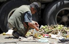 Imagen de archivo  de una persona buscando sobras de vegetales en un mercado en Bogotá, mar 7, 2012. La pobreza en Colombia se redujo a un 27,8 por ciento de la población y la indigencia a un 7,9 por ciento en 2015, pese a la desaceleración de la economía, informó el miércoles el Gobierno.  REUTERS/John  Vizcaino