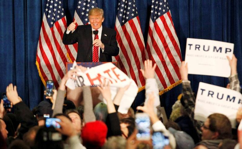 Republican U.S. presidential candidate Donald Trump gives a thumbs up as his supporters rip apart a sign being held up by protestors in front of the candidate that read ''No Place for Hate in Maine'' during a campaign rally in Portland, Maine, March 3, 2016.   REUTERS/Joel Page