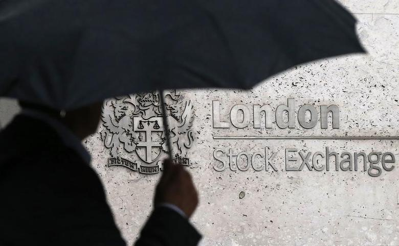 A man shelters under an umbrella as he walks past the London Stock Exchange in London, Britain August 24, 2015.REUTERS/Suzanne Plunkett