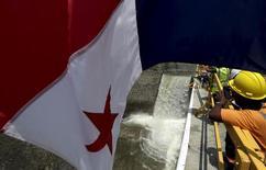 En la imagen, una bandera panameña flamea mientras trabajador observa parte de las tareas del proyecto de expansión del Canal de Panamá en las afueras de la capital, June 11, 2015. La economía de Panamá se expandió un 5.8 por ciento en 2015, su menor ritmo en cinco años, mostraron el viernes cifras oficiales, debido principalmente a la demora en el avance de grandes proyectos de infraestructura. REUTERS/Carlos Jasso
