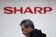 """Un peatón camina bajo el logo de Sharp Corp, afuera de una tienda en Tokio. 26 de febrero de 2016. Las conversaciones para que la firma taiwanesa Foxconn adquiera una participación mayoritaria en la japonesa Sharp van """"en el camino correcto"""", dijeron el lunes personas familiarizadas con el asunto, después de que un obstáculo de última hora sobre pasivos contingentes retrasó el mes pasado las negociaciones. REUTERS/Yuya Shino"""