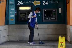 Chipre concluirá su programa de rescate con éxito a final de mes y es capaz de financiarse después de tres años de ayudas y reformas financieras, dijo lunes el presidente de los ministros de Finanzas de la zona euro. En la imagen, una señora de la limpieza friega el suelo junto a unos cajeros en una sucursal del Banco de Chipre en Nicosia, el 7 de marzo de 2016. REUTERS/Yiannis Kourtoglou