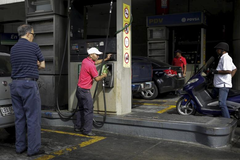 A worker handles the nozzle of a fuel dispenser at a gas station, which belongs to Venezuela's state oil company PDVSA, in Caracas, February 12, 2016. REUTERS/Marco Bello