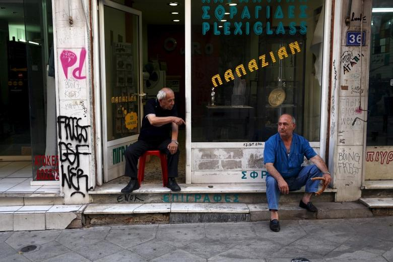 Men sit in front of a shop in central Athens, Greece, July 21, 2015.  REUTERS/Yiannis Kourtoglou  -