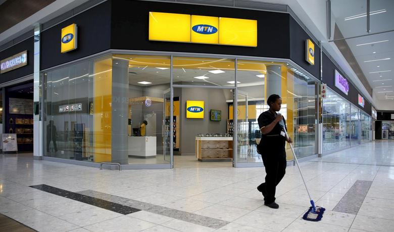 A worker sweeps past an outlet of South Africa's MTN Group in Johannesburg, February 23, 2016. REUTERS/Siphiwe Sibeko