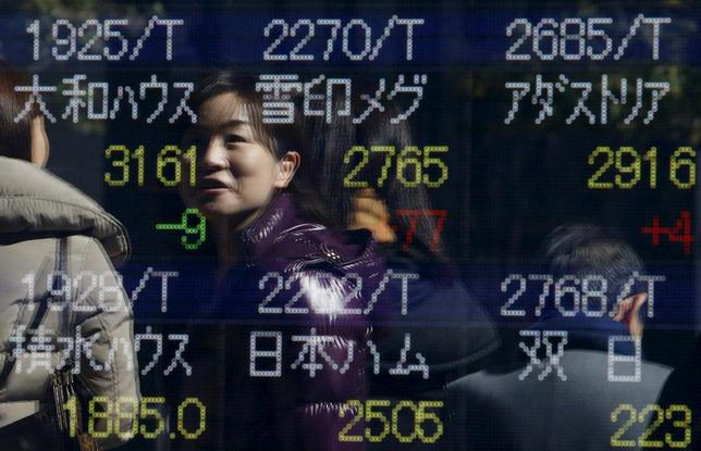 A pedestrian is reflected in an electronic board showing various stock prices outside a brokerage in Tokyo, Japan, February 26, 2016.  REUTERS/Yuya Shino