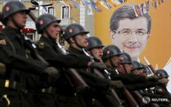 Турецкие солдаты маршируют на фоне предвыборного плаката премьер-министра Ахмета Давутоглу на параде в Стамбуле 29 октября 2015 года. Премьер-министр Турции Ахмет Давутоглу сказал, что исполнительный комитет оборонной промышленности Турции одобрил ряд оборонных проектов стоимостью $5,9 миллиарда, из которых $4,5 миллиарда будет потрачено на отечественную продукцию. REUTERS/Murad Sezer