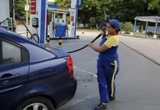 Una empleada en una gasolinera en Asunción, mar 8, 2016. El bajo precio de las materias primas, en mínimos de varios años, impulsó el aumento de las cesaciones de pagos a principios de este año, mientras el sector petrolero podría sufrir el cierre aún de sus yacimientos menos rentables, dijeron analistas de la industria el miércoles.  REUTERS/Jorge Adorno