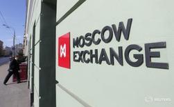 Мужчина входит в здание Московской биржи 14 марта 2014 года. Российские фондовые индексы, обновившие пики года в официально выходной понедельник, скорректировались в начале торгов среды и большую часть сессии провели у достигнутых значений, а на новые максимумы взошли бумаги ИнтерРАО и Россетей. REUTERS/Maxim Shemetov