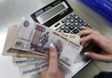 Сотрудник магазина пересчитывает рублевые купюры в Красноярске 21 января 2016 года. Рубль пошел в рост после плоского биржевого открытия четверга, обновив максимумы текущего года с оглядкой на Brent, которая сократила внутридневные потери и подходила к отметке $41 за баррель, а также с расчетом на новые стимулирующие меры от ЕЦБ по итогам сегодняшнего заседания регулятора, которые могут поддержать высокорискованные активы. REUTERS/Ilya Naymushin