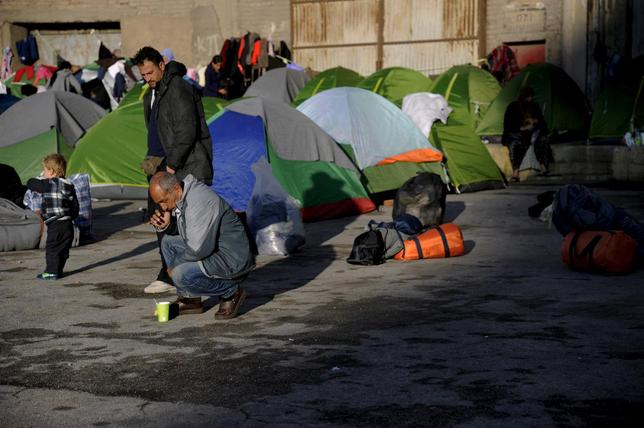Refugees and migrants are seen by their tents, next to an old building at the port of Piraeus, near Athens, Greece, March 10,  2016. REUTERS/Michalis Karagiannis