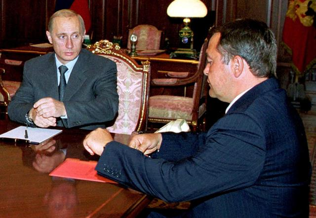 Russian President Vladimir Putin (L) listens during his meeting with Minister for Mass Media Mikhail Lesin (R) in the Kremlin in this August 28, 2000 file photo.  REUTERS/Files