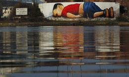 A huge graffiti artwork of toddler Aylan Kurdi, by Frankfurt artists Justus Becker and Oguz Sen is seen on a wall on the banks of river Main near the headquarters of the European Central Bank in Frankfurt, Germany, March 10, 2016.  REUTERS/Kai Pfaffenbach