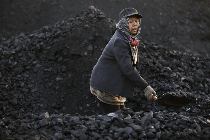 A villager moves coal at local businessman Sun Meng's small coal depot near a coal mine of the state-owned Longmay Group on the outskirts of Jixi, in Heilongjiang province, China, October 23, 2015. REUTERS/Jason Lee