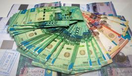 Купюры валюты тенге в отделении Евразийского банка в Алма-Ате 15 января 2015 года. Чистая прибыль Халык-банка выросла в 2015 году до 120,3 миллиарда тенге со 114,4 миллиарда тенге в 2014 году, что выше прогнозов банка и аналитиков, сообщил Халык в понедельник. REUTERS/Shamil Zhumatov