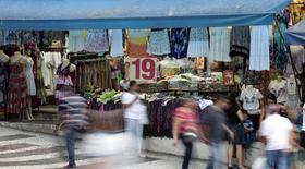 Personas caminan delante de una tienda en una calle comercial en el centro de Sao Paulo, 4 de diciembre de 2014. La actividad económica en Brasil cayó en enero en una base ajustada estacionalmente, mostraron datos oficiales el lunes, destacando las perspectivas de que la recesión en el país sudamericano ha seguido empeorando al inicio de este año.   REUTERS/Paulo Whitaker