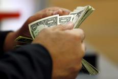 Клиент банка в Каире пересчитывает доллары США. Валютные рынки относительно спокойны в понедельник после значительных колебаний на прошлой неделе, так как инвесторы приготовились к заседаниям японского и американского центробанков в надежде получить новые указания на возможные сроки подъема процентных ставок. REUTERS/Amr Abdallah Dalsh