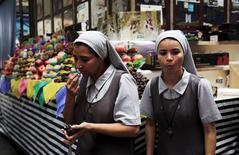 Unas monjas comiendo uvas tras haberlas comprado en el mercado municipal de Sao Paulo, ene 7, 2016. Las expectativas inflacionarias para fines de 2016 en Brasil bajaron la semana pasada tras un aumento por debajo de lo esperado en los precios al consumidor de febrero, mostró el sondeo semanal Focus del banco central el lunes.  REUTERS/Nacho Doce