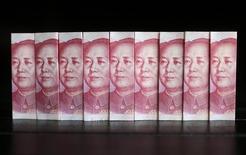 Ilustración fotografíca realizada en Pekín con billetes de 100 yuanes, jul 11, 2013. Las ventas netas de divisas del banco central chino bajaron a 227.900 millones de yuanes (35.100 millones de dólares) en febrero desde los 644.500 millones de yuanes de enero, indicando menos intervenciones del organismo monetario para apuntalar la moneda local, ante una reducción de la salida de capitales.  REUTERS/Jason Lee