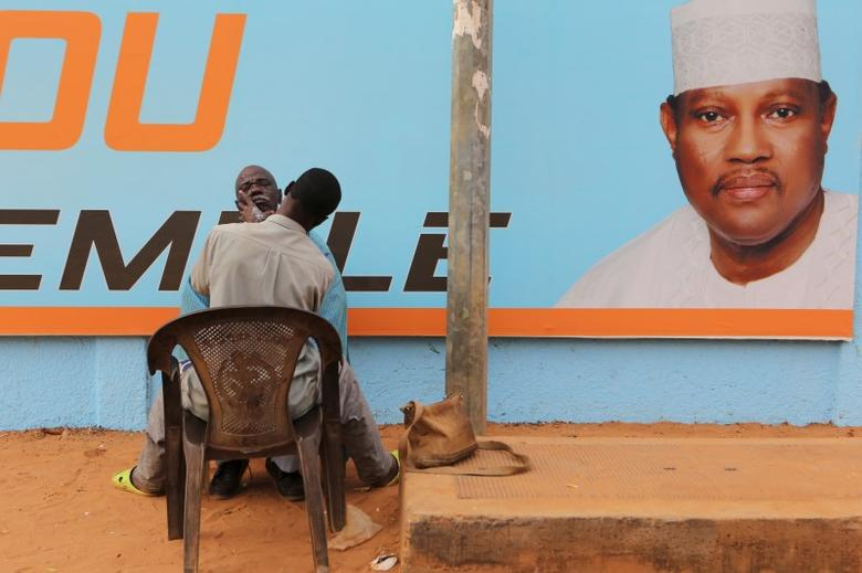 A man gets a haircut and a shave in front of a campaign poster of incarcerated opposition candidate Hama Amadou in Niamey, Niger, February 15, 2016.  REUTERS/Joe Penney