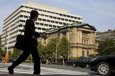 Мужчина проходит мимо здания Банка Японии в Токио 30 октября 2015 года. Банк Японии оставил монетарную политику без изменений во вторник, однако озвучил более пессимистичную оценку экономики и предупредил об ослаблении инфляционных ожиданий, сигнализируя о том, что глобальные сдерживающие факторы могут привести к расширению мер стимулирования. REUTERS/Thomas Peter