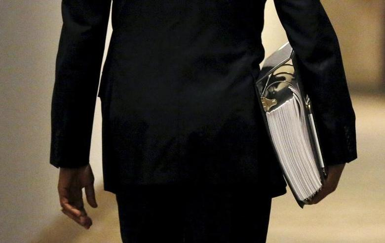 U.S. President Barack Obama carries a binder containing material on potential Supreme Court nominees as he walks towards the residence of the White House in Washington February 19, 2016. REUTERS/Kevin Lamarque