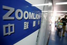 A Zoomlion company logo is seen on an advertisement as passengers walk past at an airport in Changsha, Hunan province July 13, 2013. REUTERS/Stringer