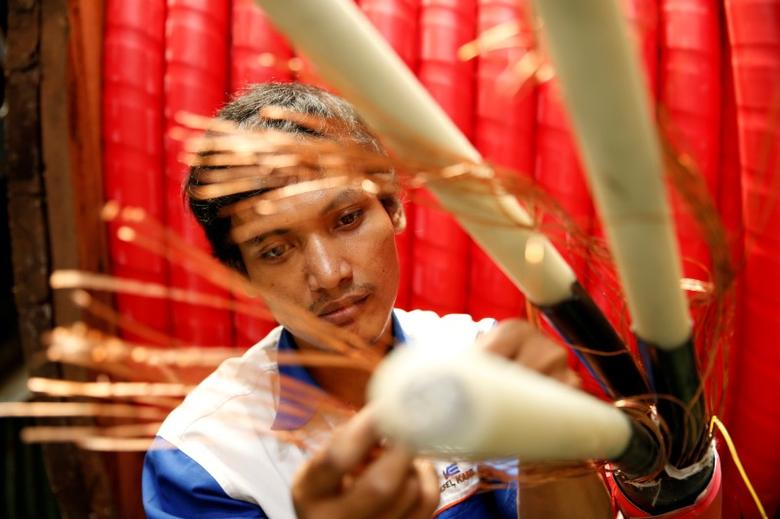 A worker counts copper wires at PT Voksel Electric at Cibubur district on the outskirts of Jakarta August 23, 2013.  REUTERS/Beawiharta