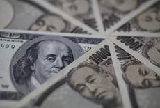 Купюры валют доллар США и иена в Токио 28 февраля 2013 года. Доллар в пятницу держится вблизи минимума 17 месяцев по отношению к иене, достигнутого в ходе ночных торгов после решения ФРС США уменьшить количество планируемых до конца этого года повышений ключевой ставки. REUTERS/Shohei Miyano