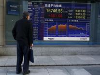 Мужчина изучает котировки на табло у биржи в Токио 2 марта 2016 года. Японские фондовые индексы завершили торги пятницы в минусе четвертую сессию подряд, так как ночное падение доллара США до 17-месячного минимума по отношению к иене оказало давление на экспортные компании и подпортило общее настроение участников рынка. REUTERS/Thomas Peter