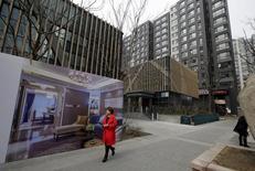 Los precios de las casas en China subieron a su mayor ritmo en casi dos años en febrero, gracias a una fuerte demanda en las grandes ciudades, pero los riesgos de sobrecalentamiento en algunas zonas combinados con un débil crecimiento en ciudades pequeñas amenazan con lastrar a una economía en desaceleración. En la imagen, una mujer camina delante de un anuncio delante de un apartamento de lujo en Pekín, China, el 15 de marzo de 2016. REUTERS/Jason Lee