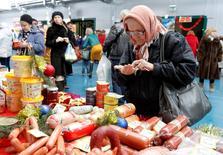 Женщина пересчитывает деньги на продовольственной ярмарке. Банк России видит, что риски в ценовой динамике на сегодняшний день распределены несимметрично и в значительной степени смещены в сторону проинфляционных, и, по его прогнозу, во втором квартале 2016 года возможно некоторое повышение годовой инфляции из-за низкой базы сравнения.  REUTERS/Eduard Korniyenko