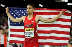 Matthew Centrowitz of the U.S. celebrates with his country's flag after winning the men's 1500 meters final during the IAAF World Indoor Athletics Championships in Portland, Oregon March 20, 2016.  REUTERS/Lucy Nicholson