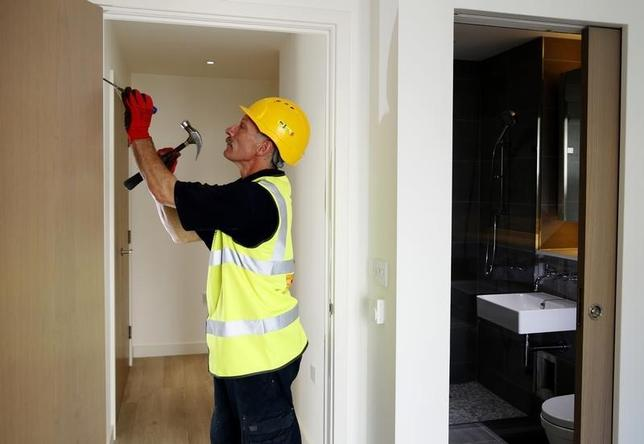 A carpenter adjusts a door in a new apartment constructed by Berkeley Homes in Hackney, northeast London July 22, 2014.  REUTERS/Luke MacGregor
