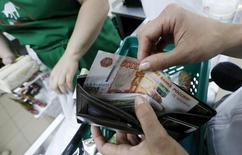 Покупатель достает деньги из кошелька в продуктовом магазине в Красноярске. 6 августа 2015 года. Реальная заработная плата в РФ в феврале 2016 года выросла на 0,4 процента к предыдущему месяцу и снизилась на 2,6 процента к февралю 2015 года, составив в номинальном выражении 32.990 рубля, сообщил Росстат. REUTERS/Ilya Naymushin