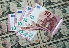 """Евро на фоне долларов. Доллар немного вырос в понедельник, восстановившись после падения более чем на 1 процент к основным валютам на прошлой неделе, так как инвесторы оправились от """"голубиных"""" комментариев Федрезерва США.  REUTERS/Heinz-Peter Bader"""