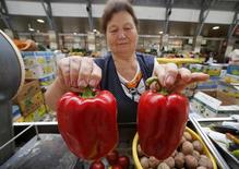 A vendor holds bell peppers from Crimea as she displays them at the city market in St.Petersburg August 7, 2014. Moscow imposed a total ban on imports of many Western foods on Thursday in retaliation against sanctions over Ukraine, a stronger than expected measure that isolates Russian consumers from world trade to a degree unseen since Soviet days. REUTERS/Alexander Demianchuk (RUSSIA - Tags: POLITICS AGRICULTURE FOOD BUSINESS)