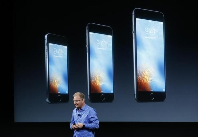 3月21日、米アップルは、上位機種の性能と比較的低い価格を併せ持つ新しい小型iPhone「SE」を発表した。写真は発表イベントでSEを披露するiPhone・iOS製品販促担当副社長のグレッグ・ジョスウィアック氏 。カリフォルニア州アップル本社で撮影(2016年 ロイター/Stephen Lam)