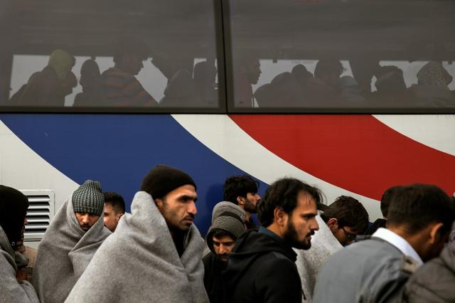 Refugees and migrants wait to be transferred to the Moria registration centre after arriving at the port of Mytilene on the Greek island of Lesbos, following a rescue operation by the Greek Coast Guard at open sea, March 22, 2016. REUTERS/Alkis Konstantinidis