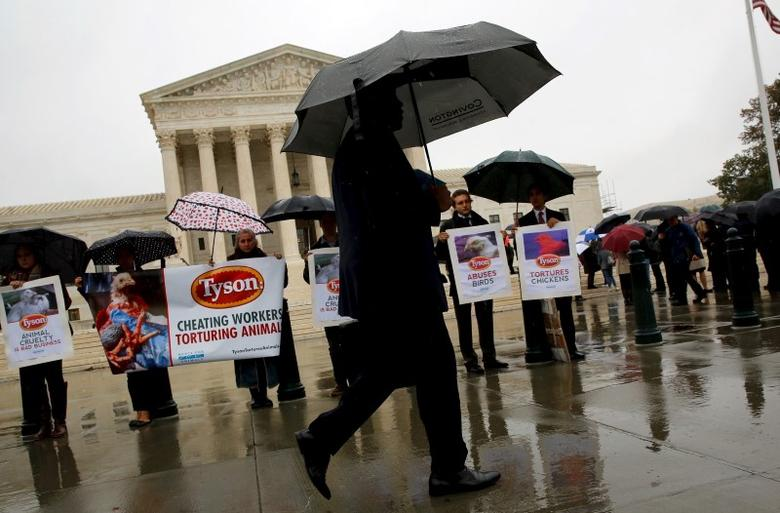 A man walks past people protesting over conditions for Tyson Foods workers and animals outside the U.S. Supreme Court in Washington November 10, 2015.   REUTERS/Jonathan Ernst