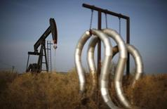 A pump jack and pipes are seen on an oil field near Bakersfield on a foggy day, California January 18, 2015. REUTERS/Lucy Nicholson