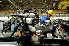 An employee works on an assembly line producing automobiles at a factory in Qingdao, Shandong Province, China, in this March 1, 2016 file photo. REUTERS/Stringer/Files